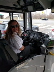 Image shows her behind the wheel.