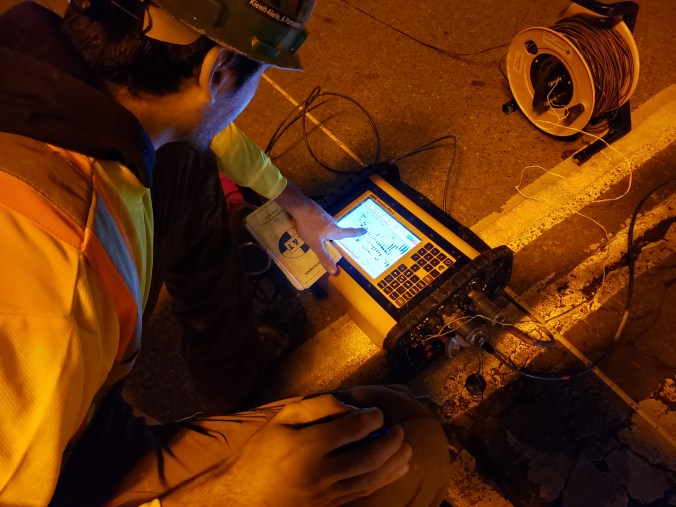 An expert looks at a device used on a street.