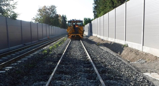 A maintenance vehicle moves along a new section of track with noise walls on either side