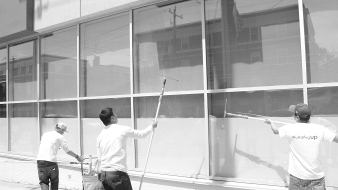 Window washers work on Eglinton Ave washing windows of street front businesses