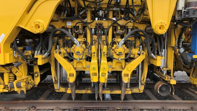Close up photo of the DynaCAT's tamping heads that adjust the rails and ties into the correct position and pack ballast underneath the track to prevent settlement