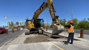 An excavator works along Hurontario while a construction worker looks on