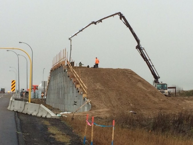 Crews work on a MSE wall.