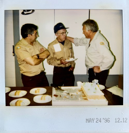 a polaroid of the Fred Bentley enjoying a slice of cake with coworkers.