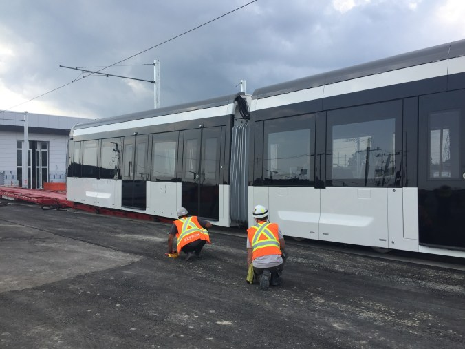 Two workers look under the LRV.