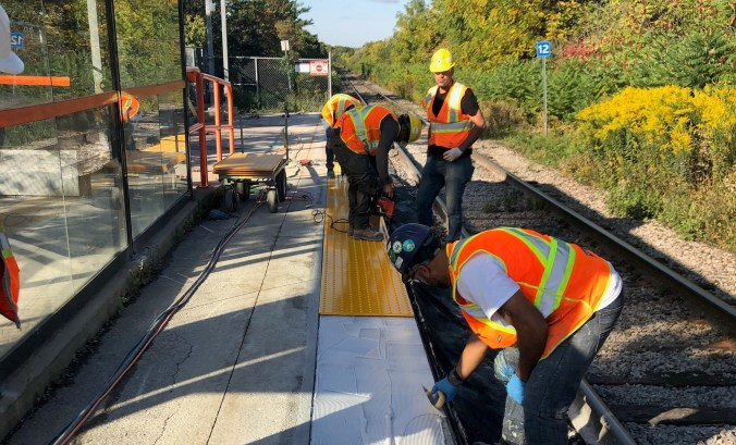 Construction crews installing yellow tactile strips on a GO station platform.
