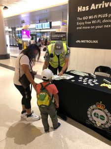 Image shows a youngster and mom talking to a GO Transit expert.
