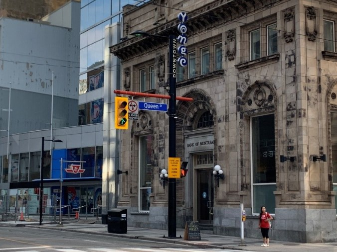A woman stands at an intersection beside the Bank of Montreal's old building.