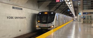 Image shows a subway train arriving at the station.