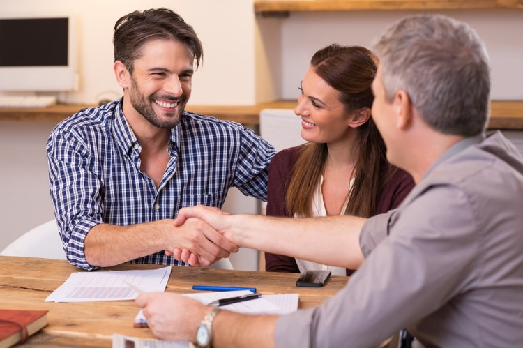 Handshake of a mature manager with a happy young couple at office. Businessmen handshake during meeting signing agreement. Happy man shaking hands whit his insurance agent to renew their insurance, improving the insurance agents retention numbers.