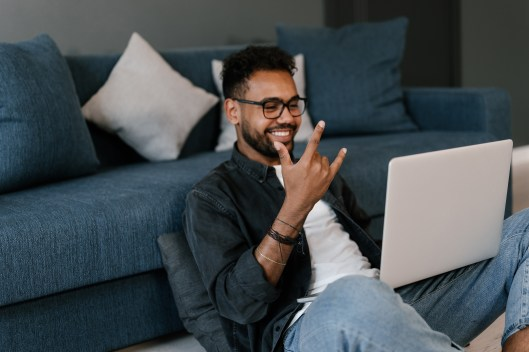 Happy ethnic guy in casual clothes and glasses smiling and calling to friends on laptop while sitting on floor near sofa at home