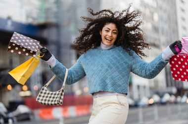happy woman jumping with shopping bags