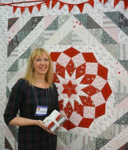 Wenche at Quilt Market, in front of the Winter Rose quilt.