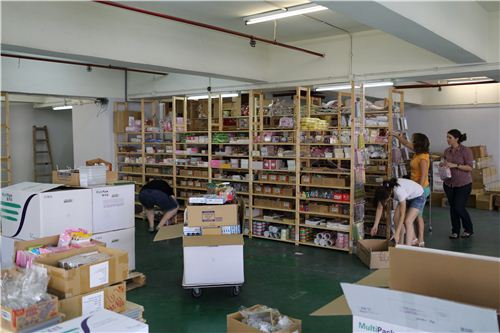 Another team is unpacking the boxes and puts the products back to the shelves