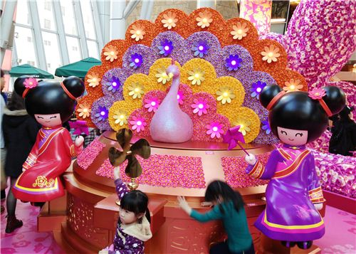 A pretty peacock with Chinese girls and a pinwheel, which brings good luck