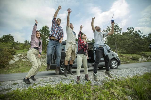 Imagem de pessoas celebrando ao lado de fora de um carro