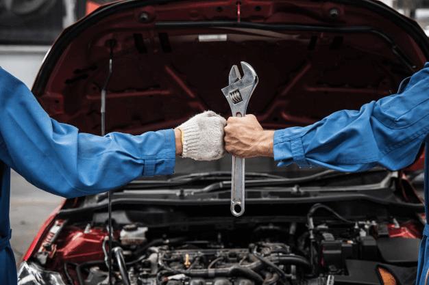 Imagem dos braços de dois mecânicos que sabem das melhores baterias de carro para seus clientes