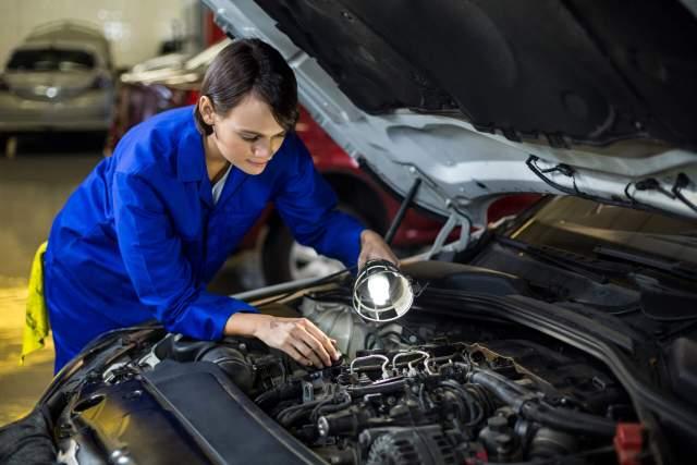 Imagem de uma mecânica verificando o cabo positivo e negativo da bateria automotiva