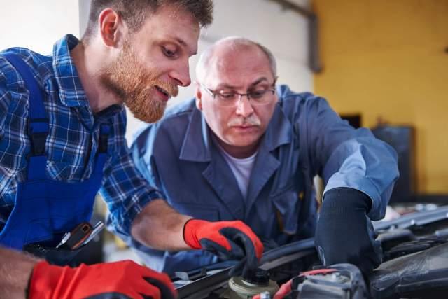 Imagem de dois mecânicos verificando painel acende mas não da partida