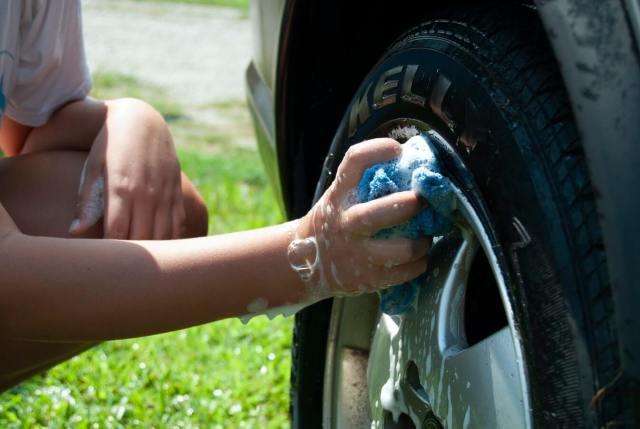 Imagem de uma mão demonstrando como lavar o carro debaixo do capô
