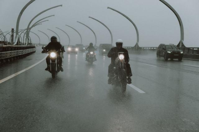 motociclistas viajando na chuva em uma autoestrada