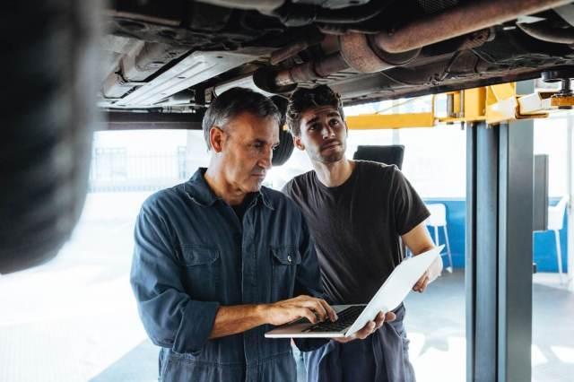 mecânico verificando no notebook detalhes sobre o veículo