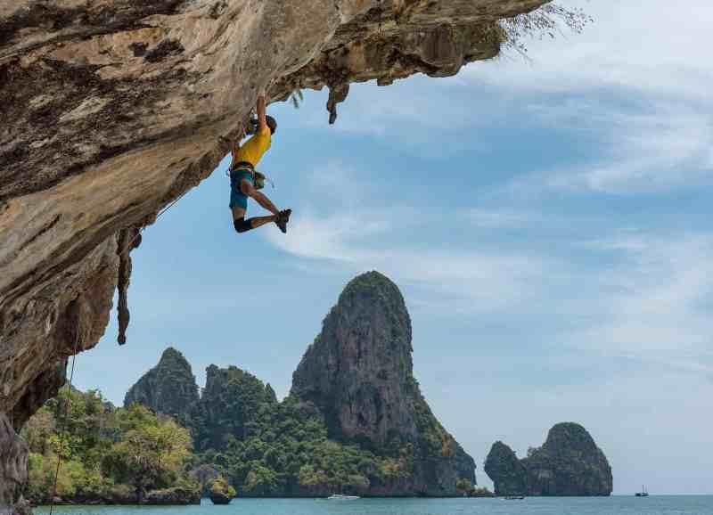 hombre escalando acantilado en la costa