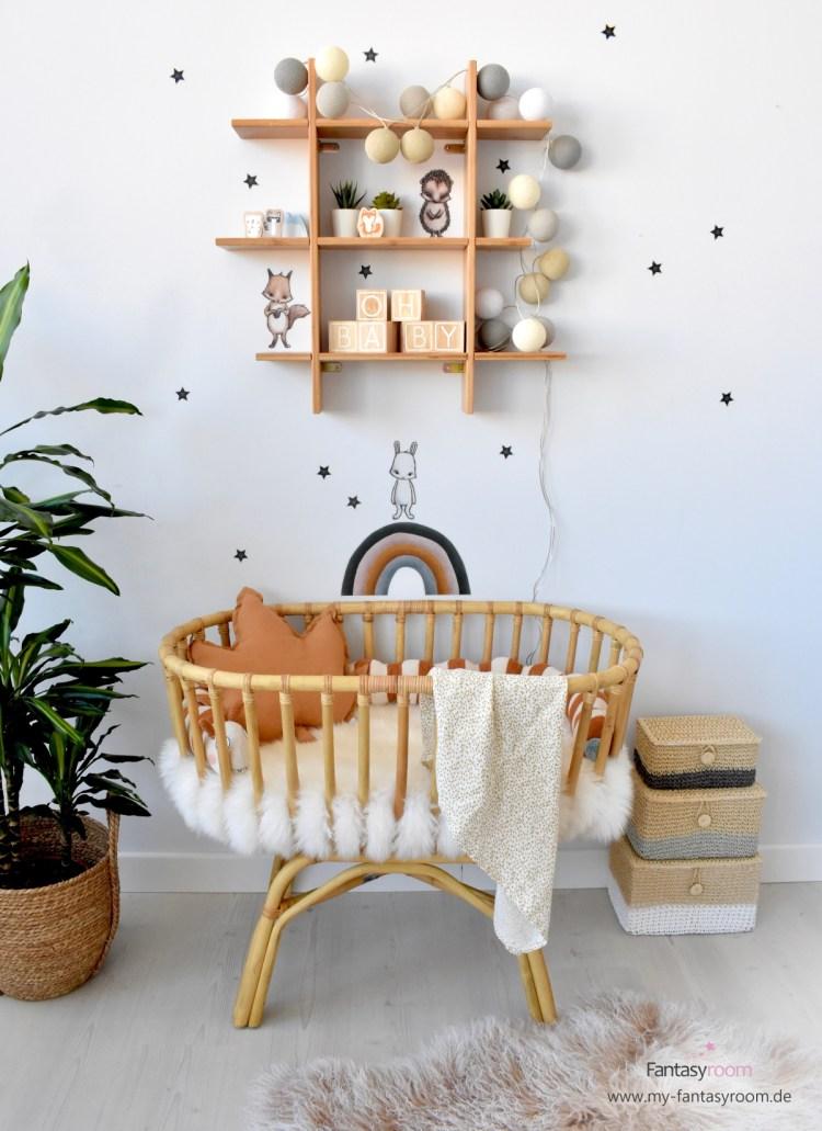 Babyecke im Wohnzimmer mit Rattanwiege und Bambus Regal