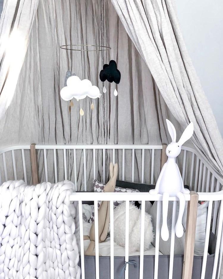 Neutrales Babybett in Weiß und Natur mit Hasenlampe und Wolkenmobile