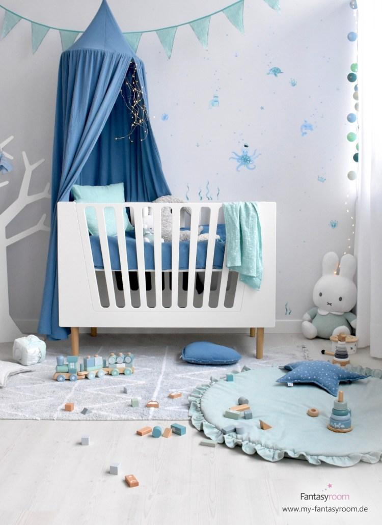 Jungenzimmer mit weißem Babybett und Deko in Mint und Blau