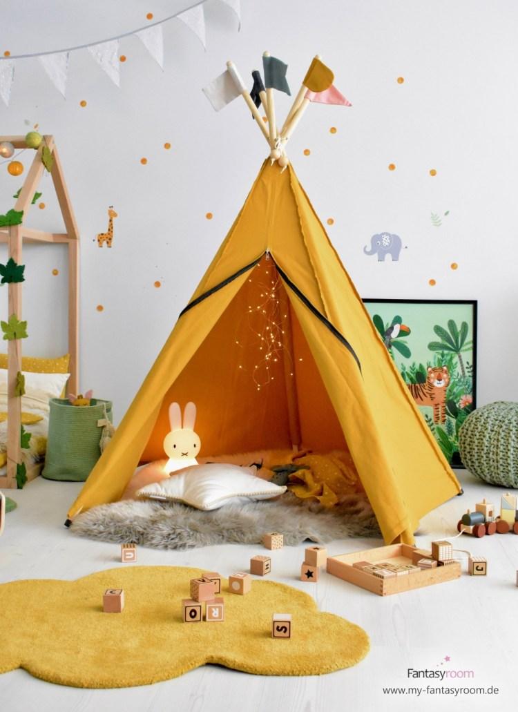 Safari Kinderzimmer mit senfgelbem Baldachin, Lammfell, MIffy Lampe und vielen Kissen
