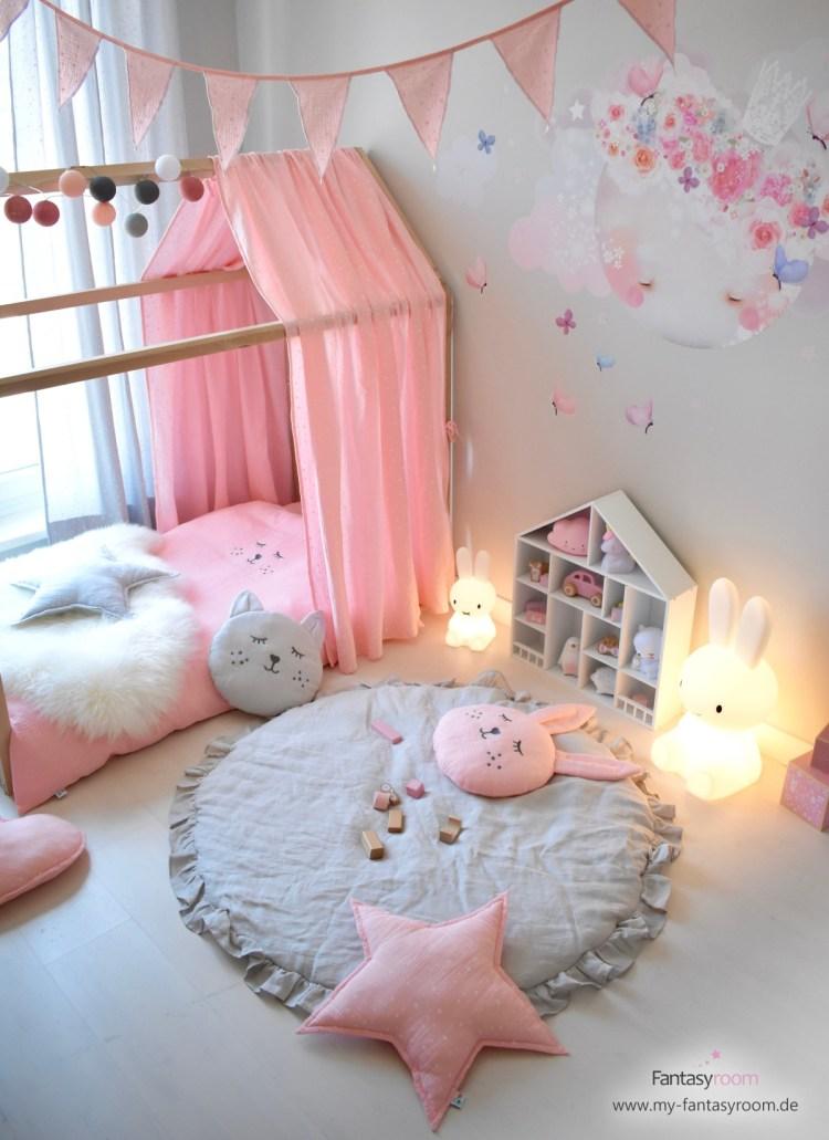 Hausbett mit rosa Musselinhimmel im romantischen Mädchenzimmer