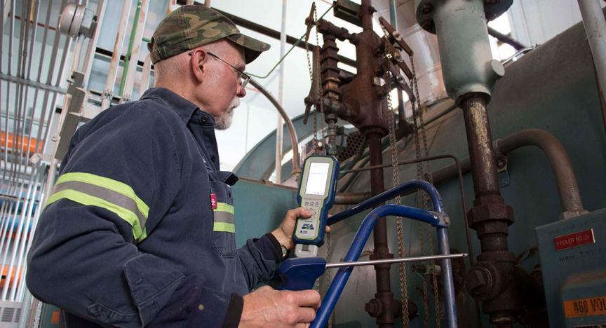 Technician preparing to test industrial boiler with PCA 400 Combustion & Emissions Analyzer.