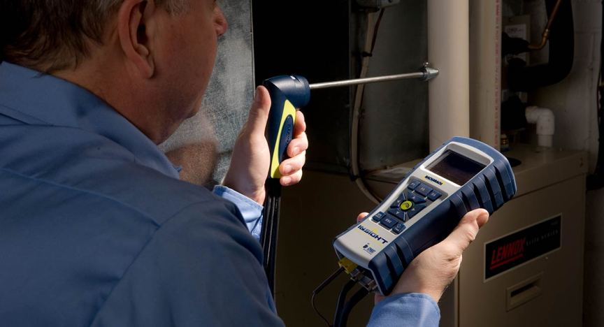HVAC technician testing residential furnace with Bacharach Insight Plus Combustion Analyzer.