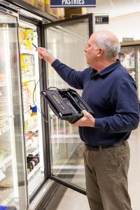 Refrigeration contractor locating refrigerant leak in supermarket.