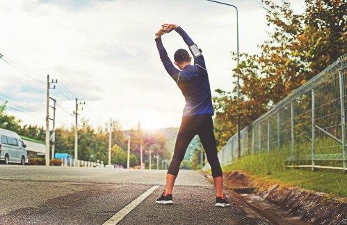 Man stretching near the roadside during a morning walk