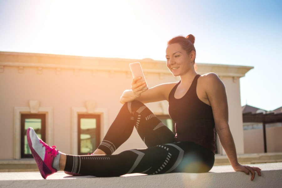 Female athlete resting outside and checking phone