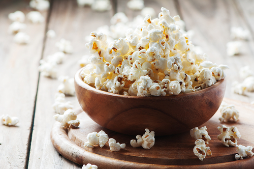 Wooden bowl overflowing with healthy popcorn