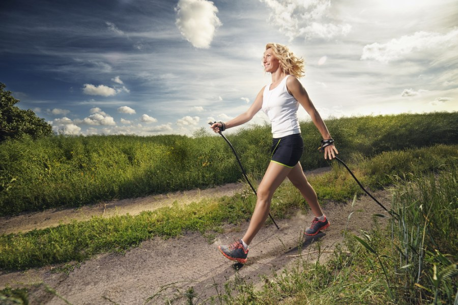 Woman Nordic walking on a green countryside path