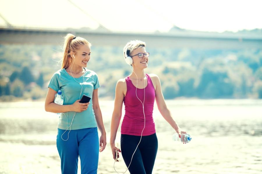 Women walking together for fitness on the beach