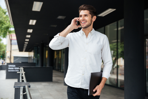 Man talking on phone outside of an office building