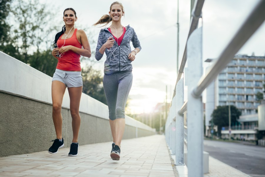 2 women jogging on a city sidewalk at morning