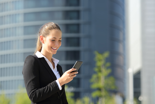 Office worker in suit checking phone outside