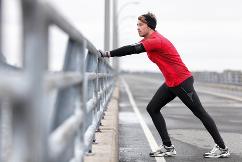 Jogger stretching calves on a bridge