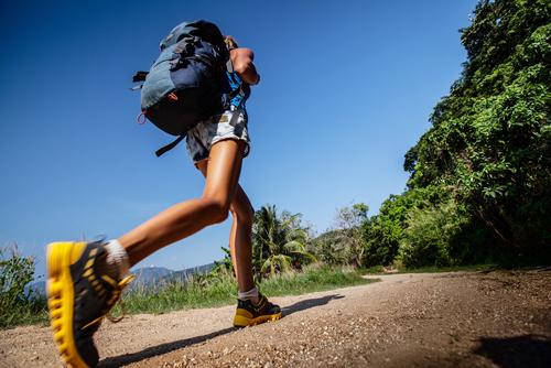 Woman incline hill walking with backback
