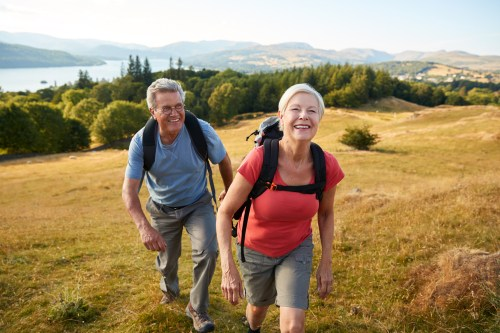 Senior couple hiking up a hill in the countryside