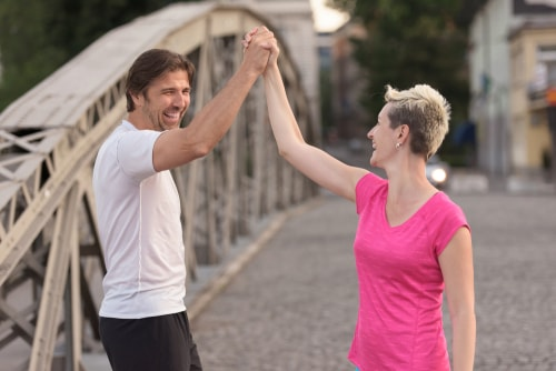 Happy walkers high fiving on a bridge