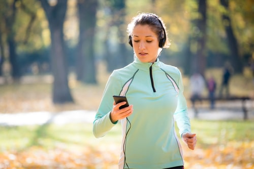 Active jogging woman checking phone
