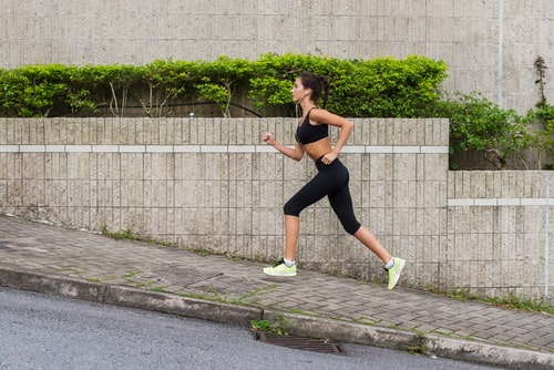 Sporty woman jogging uphill