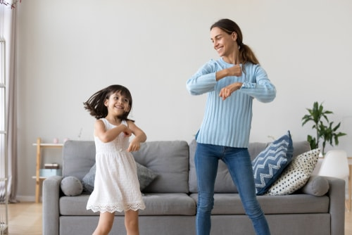 Mom and daughter dancing in living room